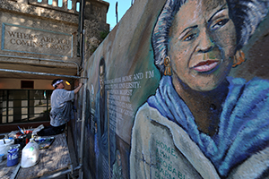 Olivia gude restores her weathered 1992 mural at 56th street and lake